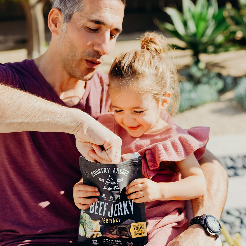 man sharing Country Archer teriyaki beef jerky with his young daughter
