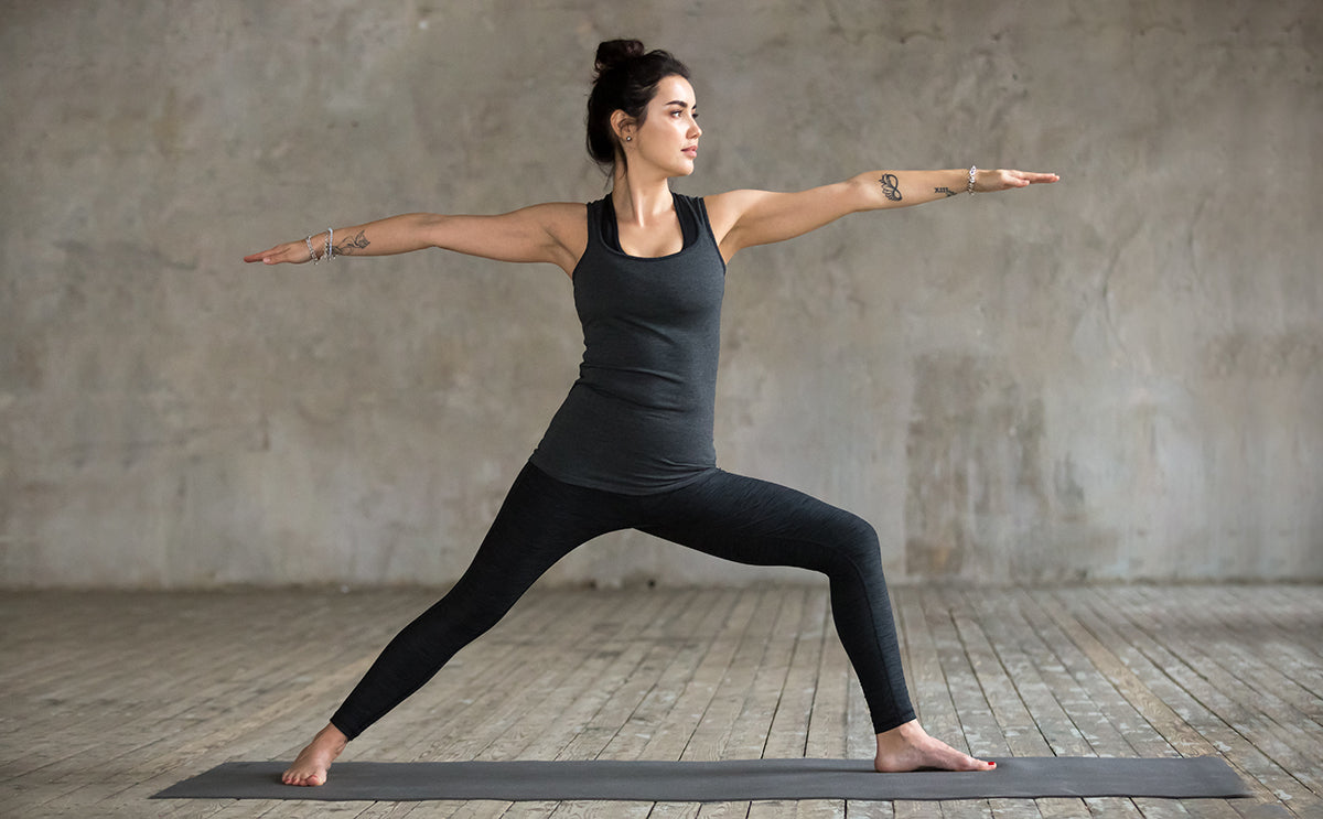 woman doing warrior two pose on yoga mat