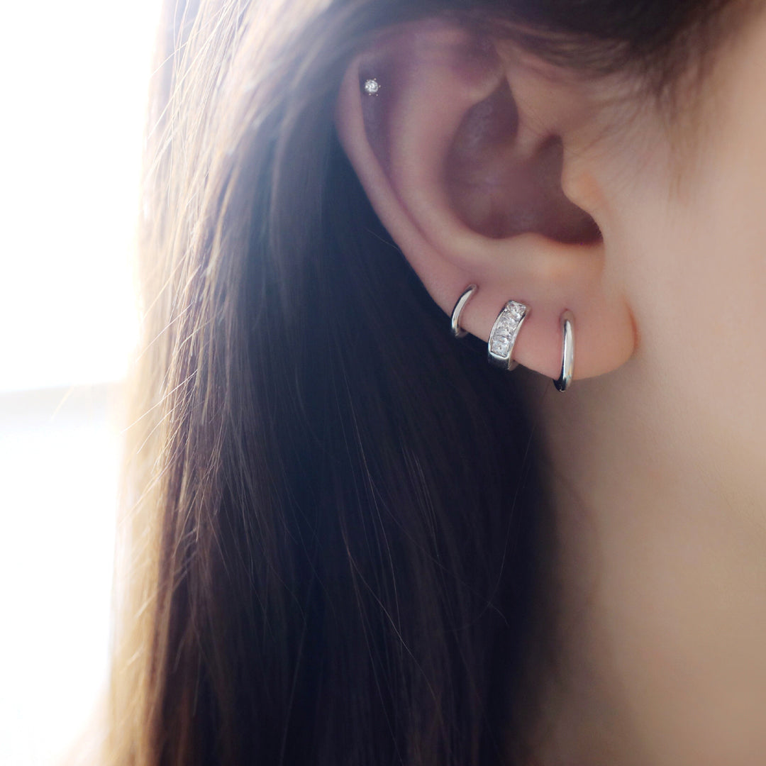 tiny stacking huggie hoops in third, second and first hole piercing