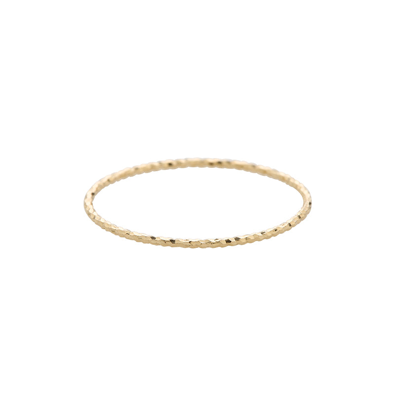 a thin textured stacking ring made from 14k gold