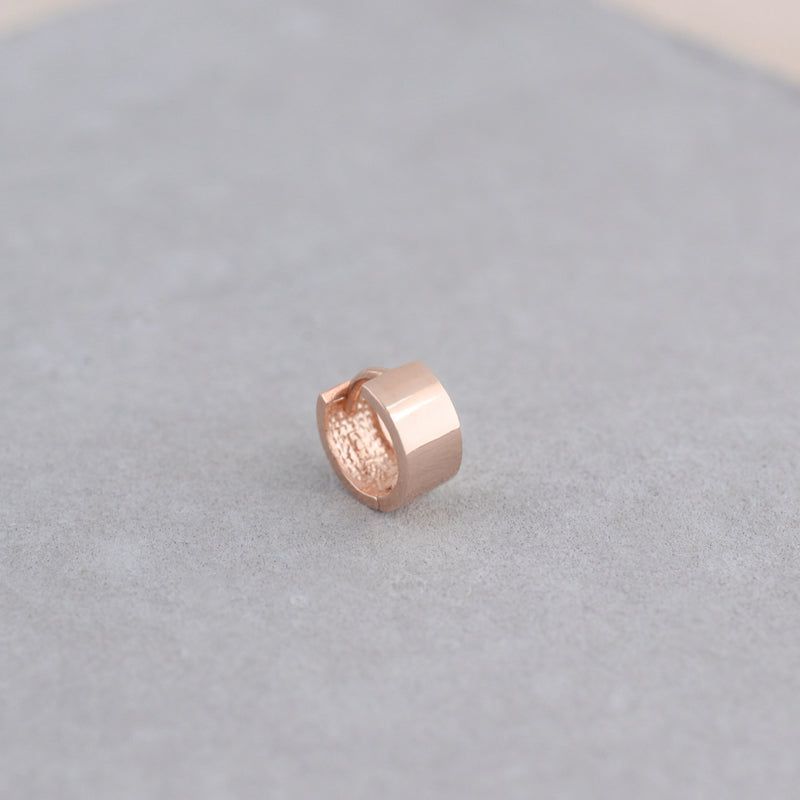 small wide huggie hoop made from 14k rose gold