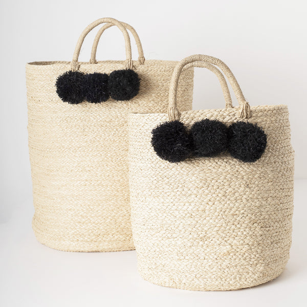 braided raffia storage basket with black pom poms