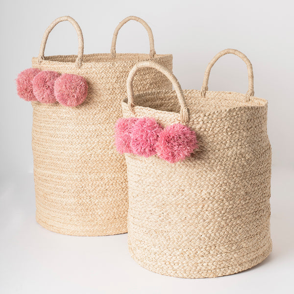 braided raffia storage basket with pink pom poms