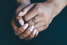 morganite gold engagement rings on hand with black backround