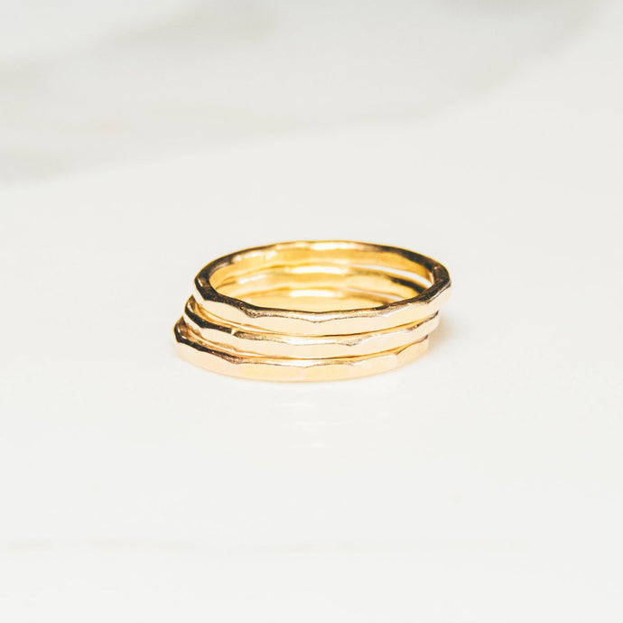 three gold faceted wedding rings bands on white marbled background