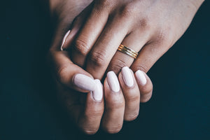 three gold wedding rings being worn on hand with black background