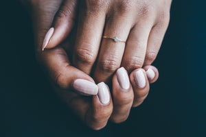 small gold diamond ring on hands with black background