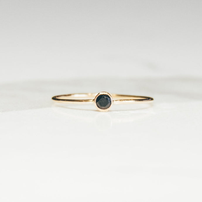 tiny black diamond on a gold band on a white and light gray marbled background