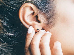 female model wearing black and gold stud earrings
