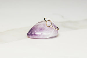 Gold circle ring on amethyst purple and white stone on white marble background