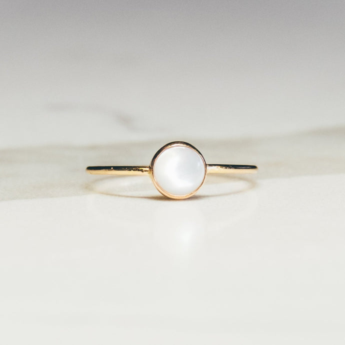 gold mother of pearl ring on white marbled background