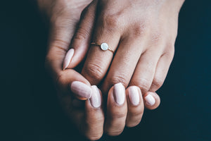 gold mother of pearl ring on hands with black background