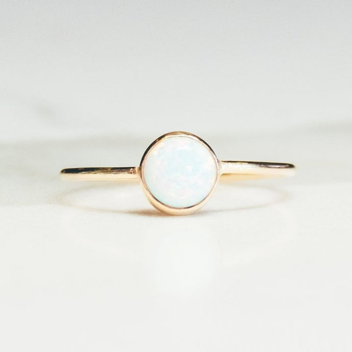 opal gold ring on white and light gray background