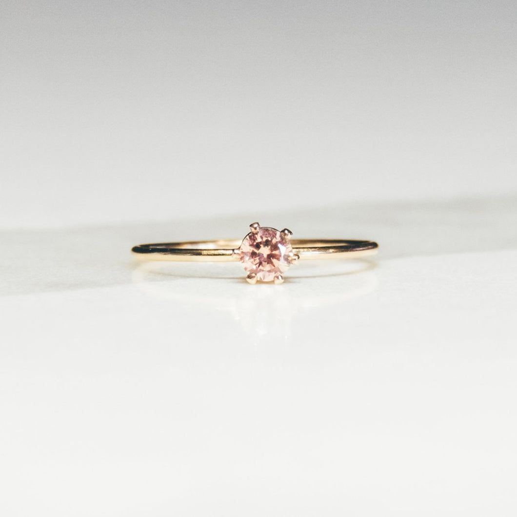 pink morganite solitaire gold ring on white and light gray marble background