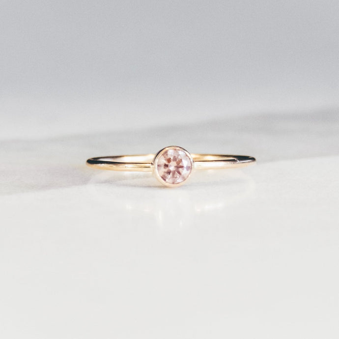 pink bezel set morganite solitaire gold ring on white and light gray marble background