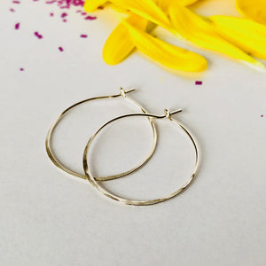 Simple hammered silver hoop earrings on white background with purple confetti and bright yellow petals