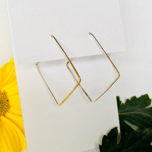 Tilted square hoop earrings hanging off of white card, with bright yellow flower in background, and dark green leaf on bottom right foreground
