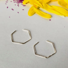 silver hexagon hoop earrings on white background with purple confetti and bright yellow petals