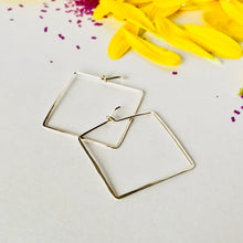 Silver square hoop earrings laying on white background, with bright yellow petals, and purple confetti