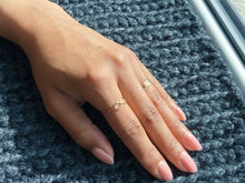delicate dainty minimalist gold infinity ring on hand on gray knit surface