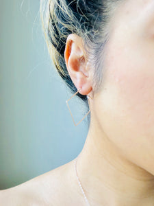 delicate silver square hoop earring being worn on ear by female model with updo wearing a necklace