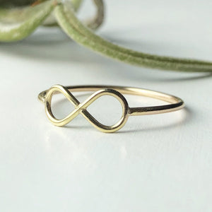 minimalist delicate dainty gold infinity ring on white background with green plant in background
