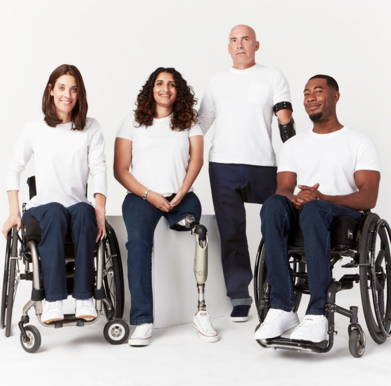 Full shot. 4 people smiling for camera. They wear white crew neck shirts and dark blue denim jeans. From left to right: a person using a manual wheelchair with camber wheels, a person using a transfemoral prosthesis, a person using a transradial prosthesis and a person using a manual wheelchair.