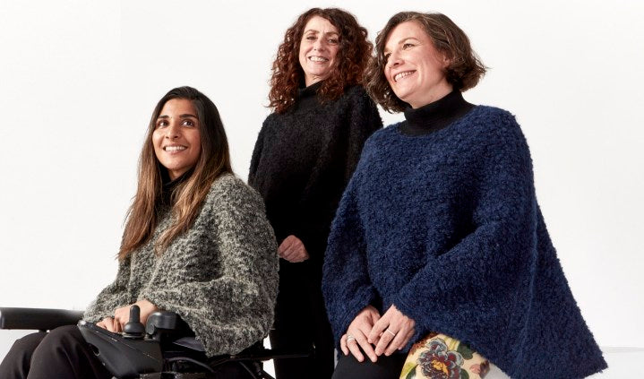 3 women smile and pose together. They wear boucle capes with turtlenecks in 3 different colors: gray, black and navy. 1 woman using a wheelchair, 1 woman standing, 1 woman sits on a block.
