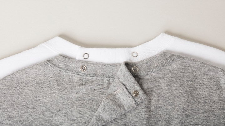 Extreme closeup. 2 t-shirts with snap back closures at collar and down the back. Gray t-shirt is on top of white t-shirt, with 1 of 2 collar snap closures unfastened to demonstrate small size of buttons.