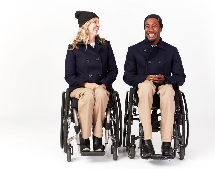Full shot, seated. 2 people using manual wheelchairs with camber wheels. They smile and laugh as they face towards camera. Both of them wear brown beanies, navy peacoats, tan jeans and black dress shoes.