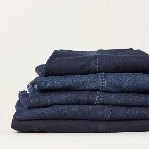 A stack of 5 denim jeans folded and stacked on top of each other. Colors range from dark blue to blue.