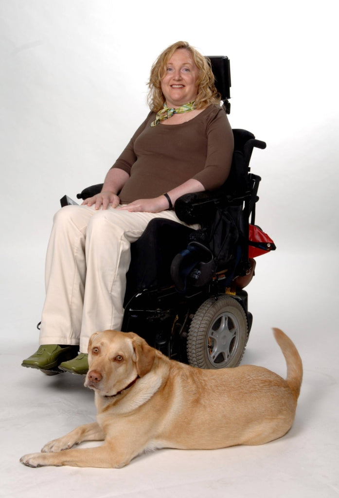 Full shot, seated. Barbara Turnbull using a power chair. She wears a brown tee, beige jeans and green loafers. A Golden Labrador lies in front of Barbara.
