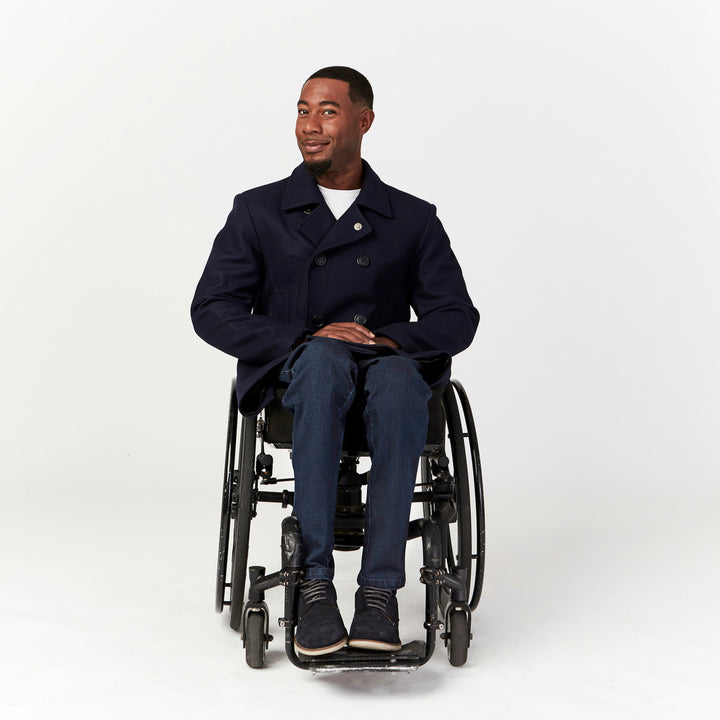 Full shot, seated. Man using manual wheelchair with camber wheels wears Indigo jeans with straight leg cut. Paired with navy peacoat, white tee and navy sneakers.