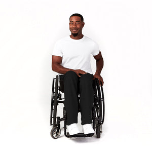 Full shot, seated. Man using wheelchair with camber wheels. His black sweatpants have a natural but sleek fit. Paired with white t-shirt and white sneakers.