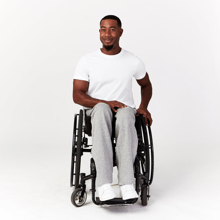 Full shot, seated. Man using manual wheelchair with camber wheels. He wears gray sweatpants with straight leg cut that drapes naturally around legs. Paired with white sneakers.
