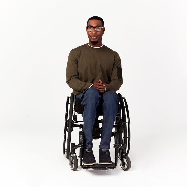 Full shot, seated. Man using manual wheelchair with camber wheels wears Indigo denim jeans with straight leg cut that comes to ankle height.