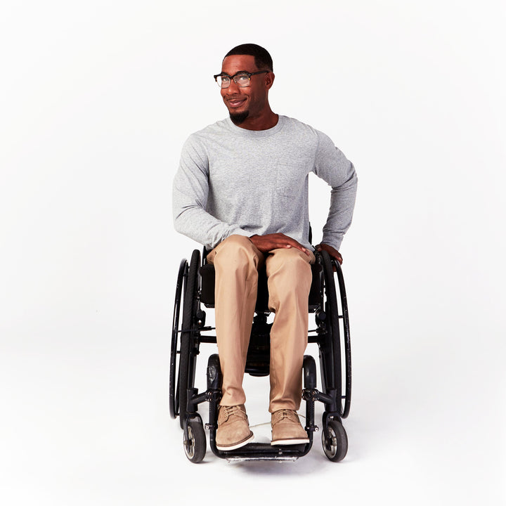 Full shot, seated. Man using manual wheelchair wears gray crew neck long sleeve tee with single breast pocket. Paired with tan chinos.