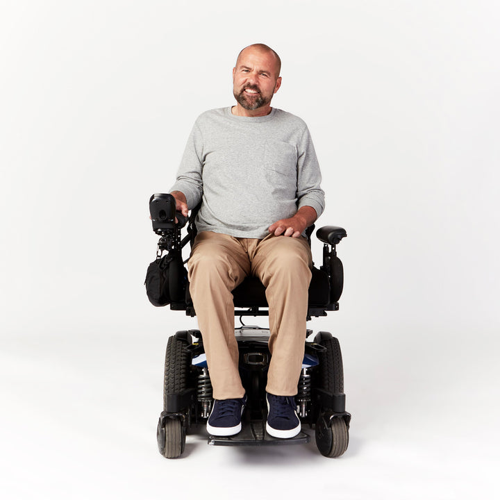 Full shot, seated. Man using power chair wears tan chino pants with straight leg hem, which fit over the ankles of his blue sneakers.