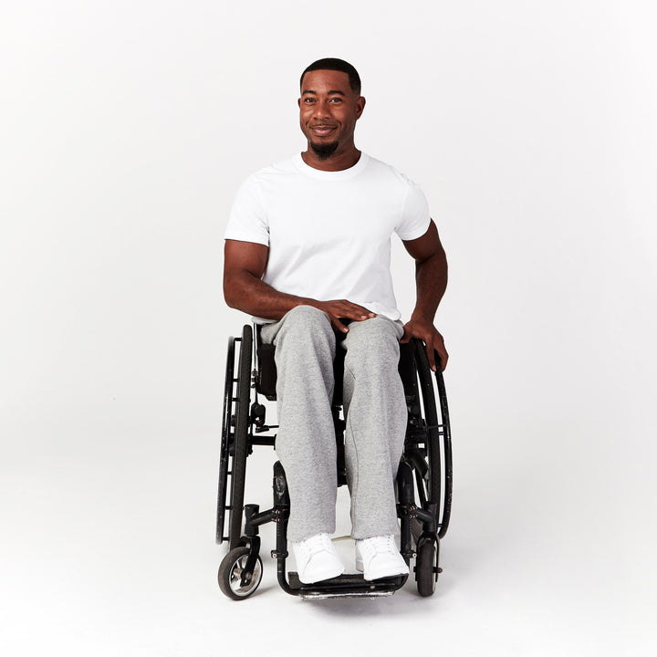 Full shot, seated. Man using manual wheelchair wears white crew neck t-shirt with short sleeves. Paired with white sneakers.