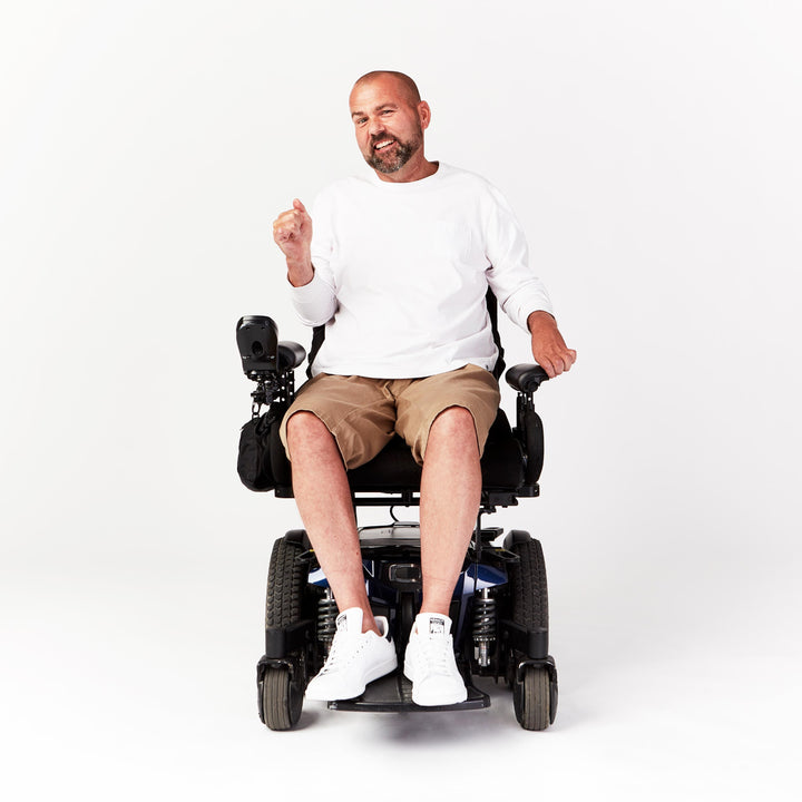 Full shot, seated. Man using power chair. He wears tan shorts with a straight leg cut that reach to the knees.