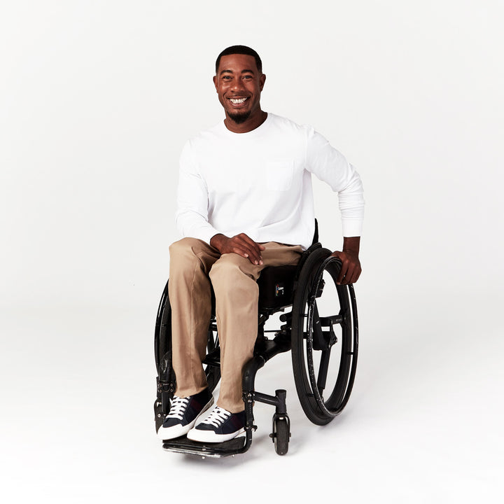 Full Shot, seated. Man using manual wheelchair wears tan chinos with straight leg hem that falls to the ankles. Outfit paired with white full-sleeved crew neck tee.