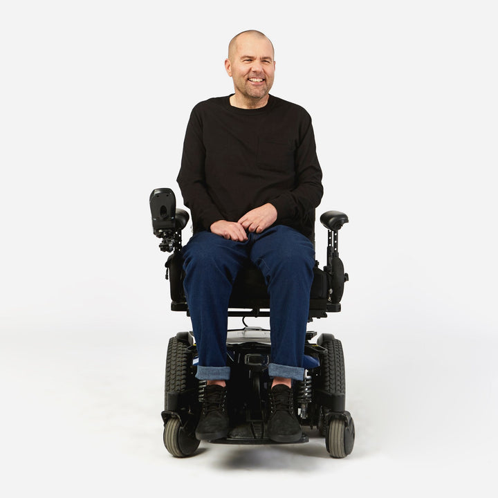 Full shot, seated. Man using power chair. He wears Indigo denim jeans with cuffs rolled once at the ankles.