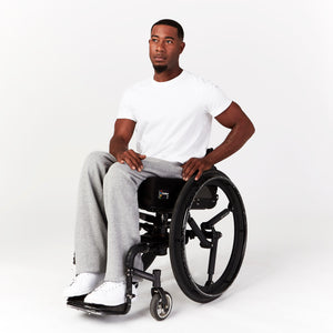 Partial side angle, seated. Man using manual wheelchair. He rests his left hand on his back wheel and twists his torso slightly, showing the comfortable seated fit of the sweatpants. Paired with white sneakers.