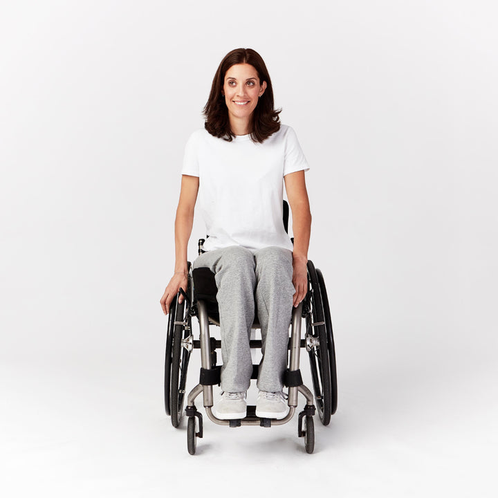 Full shot, seated. Woman using manual wheelchair with camber wheels. She wears gray sweatpants with straight leg cut that rests on tops of shoes. Paired with gray sneakers and white t-shirt.