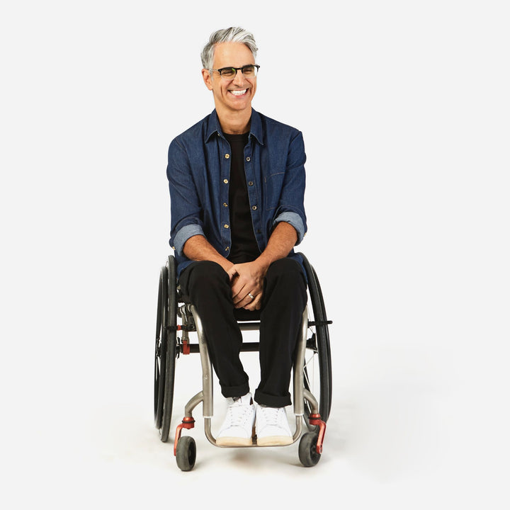 Full shot, seated. Man using manual wheelchair with camber wheels. He wears an Indigo jean shirt with magnetic closures, sleeves rolled up to elbows. Paired with black crew neck shirt, black jeans and white sneakers.