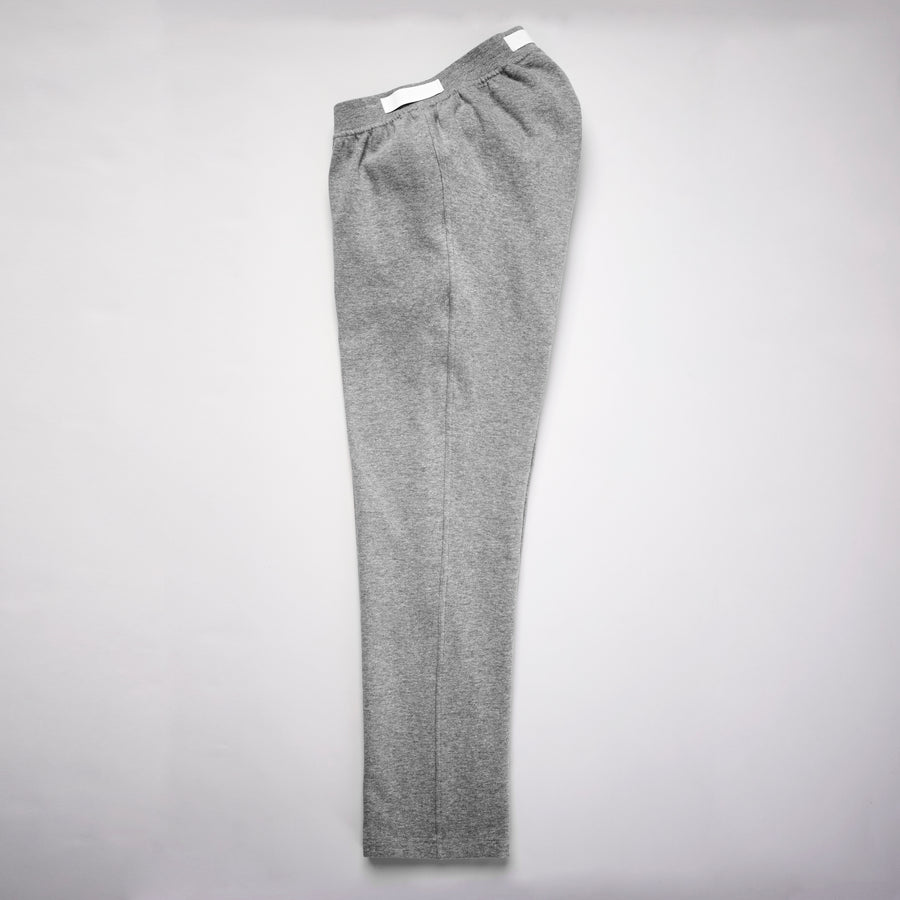 Flatlay. Gray sweatpants folded lengthwise with straight leg cut. Elastic waistband with white fabric pull tabs that sits higher in the backside. Zipper fly is fully fastened for seamless line.
