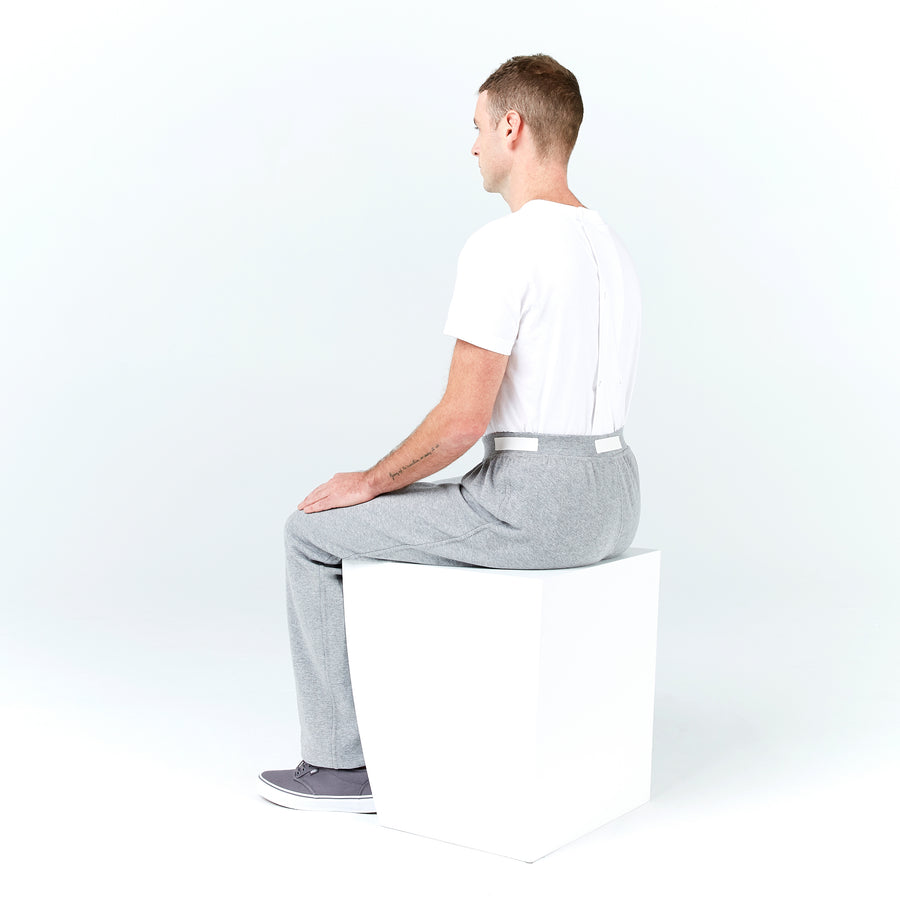 Full shot, seated. Man sits with back to camera. His gray sweatpants have an elastic waistband that rests flat against his waist. White fabric pull tabs around the waistband. Paired with gray sneakers and white t-shirt tucked into the waistband.