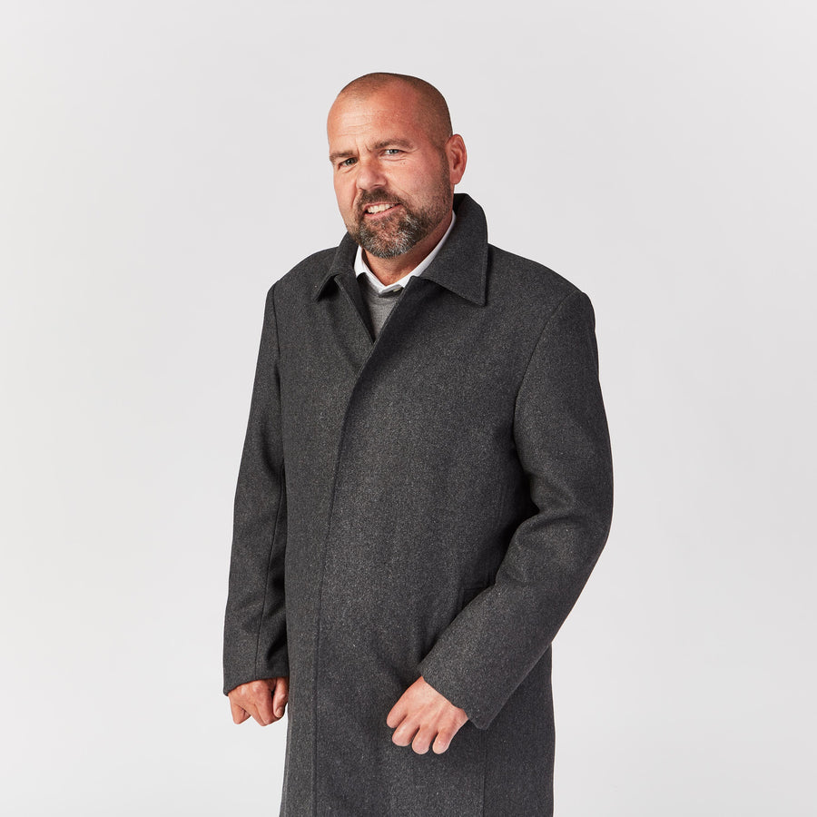 Medium shot, standing. His gray wool coat has magnetic closures fastened, providing a form-fitting but comfortable fit.