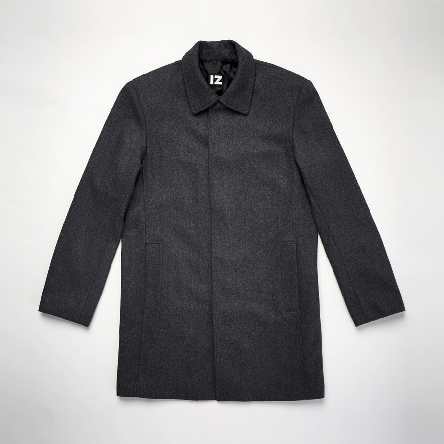 Flatlay. Gray wool coat with magnetic closures fully fastened and hidden from the outside. Coat arms lay open at sides, revealing 2 straight front pockets. Black shiny lining is visible inside the collar.