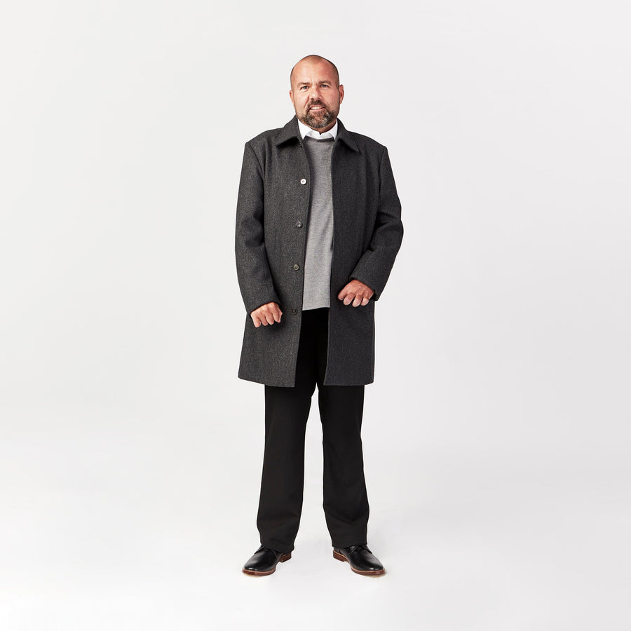 Full shot, standing. Man wears wool coat with 4 magnetic closures and flat collar. Coat has a straight drape and is layered over gray sweater and white dress shirt.